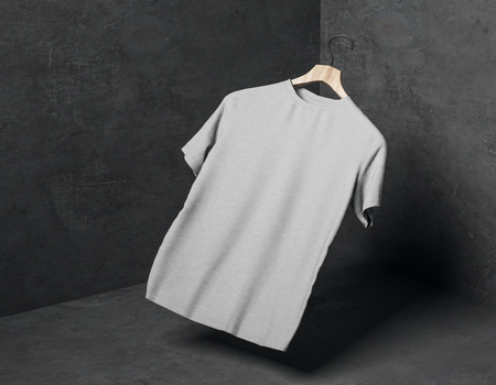 Abstract levitating grey t-shirt on hanger in concrete corner with shadow. Store, fabric, fashion and mockup concept. 3D Rendering Stock Photo - 116987879