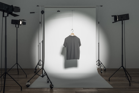 Empty black t-shirt in photo studio with professional lighting equipment. Fashion, design and mockup concept. 3D Rendering