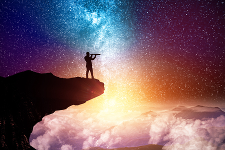 Side view of young backlit businessman on cliff looking into the distance through binoculars glass on creative starry sky space background. Vision and fantasy concept Stockfoto