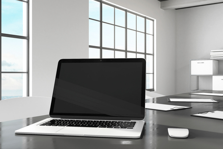 Designer desktop with empty black laptop computer screen in modern office interior. Design and ad concept. Mock up, 3D Rendering Stock Photo