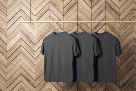 Empty three black tshirts on hanger. Wooden tile wall background. Design, store and style concept. Mock up, 3D Rendering Stock Photo