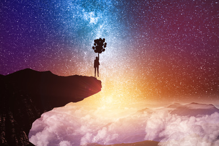 Back view of young backlit businesswoman flying with balloons on abstract starry sky space and cliff background. Freedom and fantasy concept 写真素材