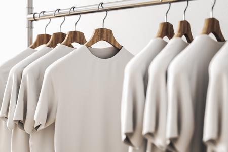 Reihe von weißen Hemden auf Kleiderbügeln. Betonwandhintergrund. Stil- und Designkonzept. 3D-Rendering Standard-Bild