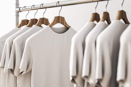 Row of white shirts on hangers. Concrete wall background. Style and design concept. 3D Rendering