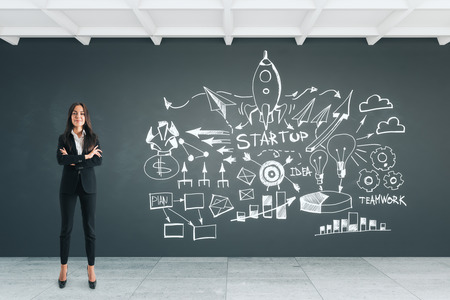 Attractive young european businesswoman standing in concrete office interior with start up sketch on wall. Startup and finance concept