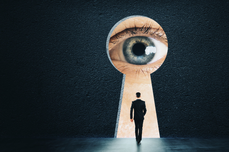 Abstract keyhole opening with businessman eye on concrete wall background. Access and vision concept