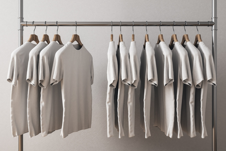 Row of white tshirts on hangers. Concrete wall background. Style and design concept. 3D Rendering