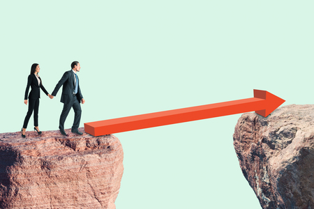 Side view of young businessman and woman walking over red arrow between two cliffs on sky background. Risk and teamwork concept Stock Photo
