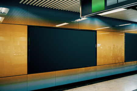 Side view of clean black subway banner on orange wall. Advertisement and urban concept. Mock up