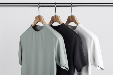 Empty grey, white and black t-shirts on hanger. Concrete wall background. Design, store and style concept. Mock up, 3D Rendering