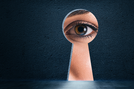 Abstract keyhole opening with eye on concrete wall background. Access and vision concept 스톡 콘텐츠