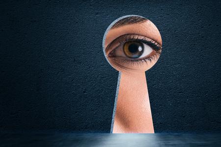 Apertura astratta del buco della serratura con l'occhio sul fondo del muro di cemento. Concetto di accesso e visione