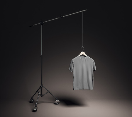 Empty gray t-shirt in photo studio with professional lighting equipment. Fashion, design and mockup concept. 3D Rendering