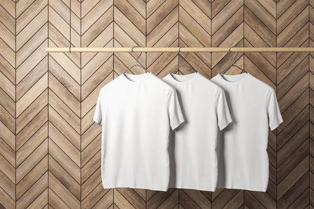 Empty three white tshirts on hanger. Wooden tile wall background. Design, store and style concept. Mock up, 3D Rendering