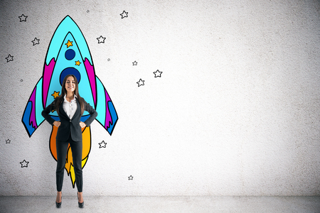 Happy young businesswoman with creative rocket sketch on concrete wall background. Startup and success concept