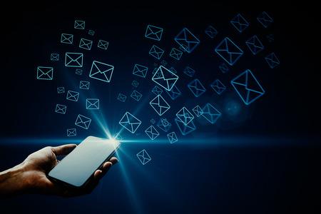 Main tenant le smartphone avec des icônes de lettres lumineuses. Concept de marketing par courrier électronique