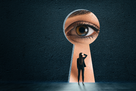 Abstract keyhole opening with businesswoman eye on concrete wall background. Access and vision concept