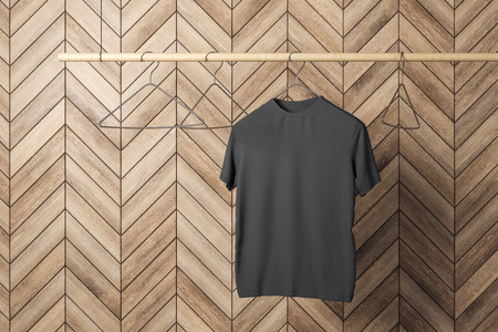Empty one black tshirt on hanger. Wooden tile wall background. Design, store and style concept. Mock up, 3D Rendering