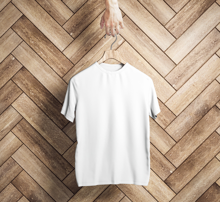 Hand holding hanger with empty white t-shirt on wooden plank wall background. Design and shop concept. Mock up, 3D Rendering