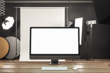 Close up of creative designer desktop with blank white computer screen in modern studio interior. Mock up, 3D Rendering Stock Photo