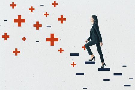 Joven empresaria subiendo escalera abstracta más y menos sobre fondo de muro de hormigón. Concepto de medicina, salud y ambición. Foto de archivo