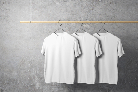 Empty three white tshirts on hanger. Concrete wall background. Design, store and style concept. Mock up, 3D Rendering
