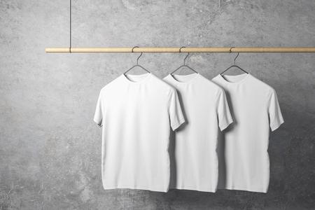 Svuota tre magliette bianche sul gancio. Sfondo muro di cemento. Design, negozio e concetto di stile. Mock up, rendering 3D