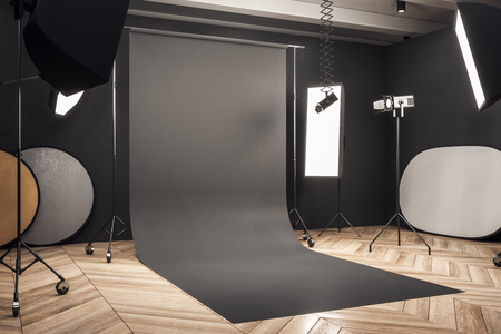 Side view of modern photo studio interior with black background, professional equipment and wooden floor. Mock up, 3D Rendering