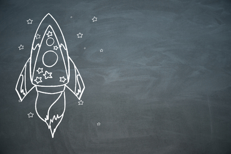Creative rocket sketch on chalkboard wall background. Startup and entrepreneurship concept