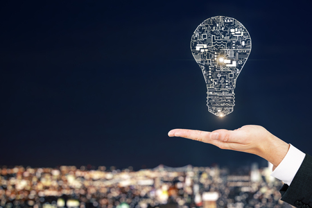 Hand holding abstract circuit lamp on blurry illuminated night city background. Engineering and power concept. Stock Photo