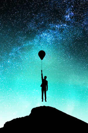 Backlit person with balloons on hill standing on beautiful starry night sky space background. Freedom and future concept Stock Photo