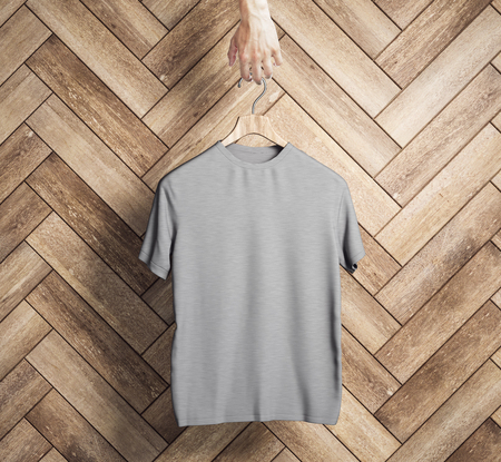 Hand holding hanger with empty grey t-shirt on wooden plank wall background. Design and shop concept. Mock up, 3D Rendering Banco de Imagens