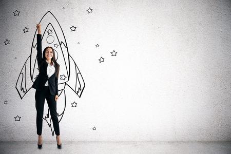Gelukkig jonge zakenvrouw met creatieve raket schets op betonnen muur achtergrond. Opstart- en projectconcept