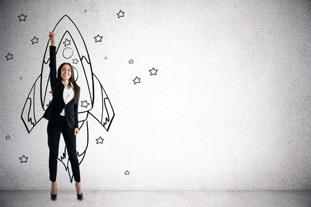 Happy young businesswoman with creative rocket sketch on concrete wall background. Startup and project concept