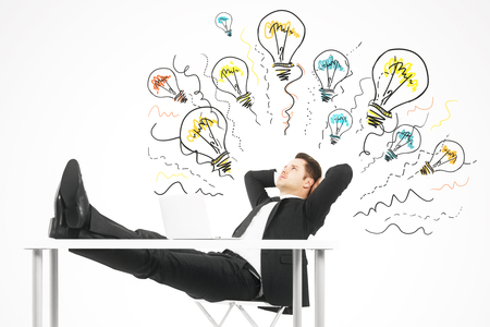 Portrait of attractive young european businessman with drawn lamps relaxing at desk with laptop on concrete wall background. Idea and solution concept