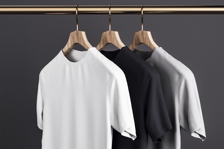 Blank grey, white and black t-shirts on hanger. Concrete wall background. Design, store and style concept. Mock up, 3D Rendering Reklamní fotografie - 117609379