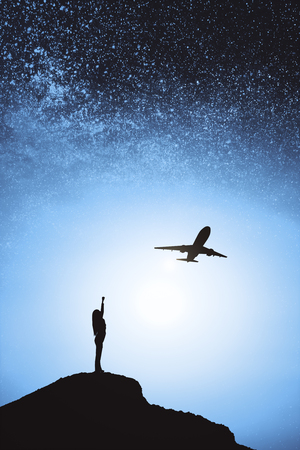 Person and airplane silhouette on hill and blurry night sky background. Freedom and travel concept