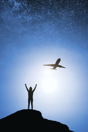 Person and airplane silhouette on hill and blurry night sky background. Success and travel concept