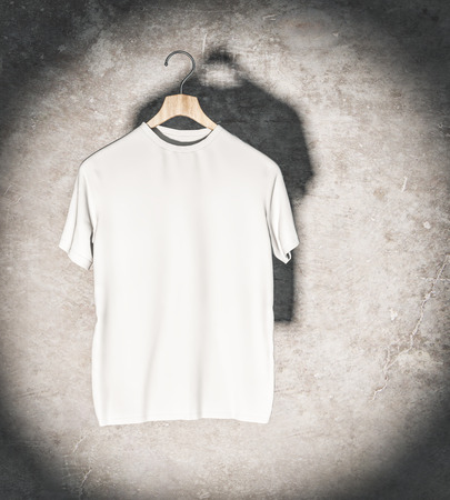 Clean white t-shirt in spotlight hanging on concrete wall. Mockup and fashion concept. 3D Rendering Banco de Imagens