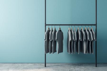 Appendiabiti con fila di magliette all'interno con copyspace vuoto sulla parete blu. Design, moda e concetto di pubblicità. Mock up, rendering 3D Archivio Fotografico