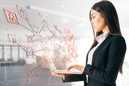 Attraktive europäische Geschäftsfrau mit Laptop unter Verwendung kreativer Geschäftsschnittstelle auf undeutlichem Büroinnenhintergrund. Bildschirm- und Social-Network-Konzept. Doppelbelichtung