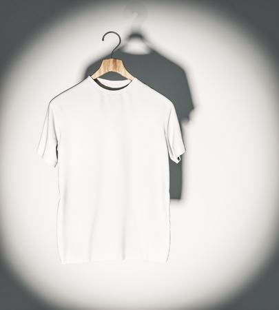 Empty white t-shirt in spotlight hanging on concrete wall. Mockup and fashion concept. 3D Rendering
