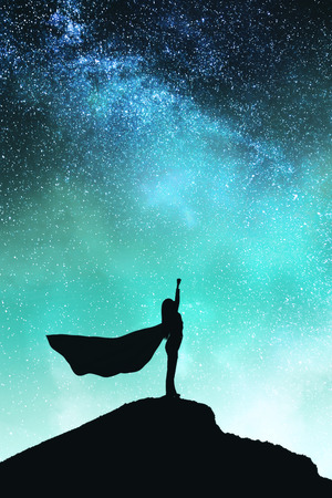 Confident backlit superhero with cape silhouette standing on mountain and starry sky background. Success and confidence concept