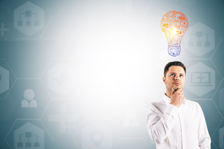Attractive thoughtful young european businessman with lamp standing on light background with copy space. Technology and inspire concept