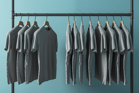 Row of grey tshirts on hangers. Blue wall background. Style and design concept. 3D Rendering