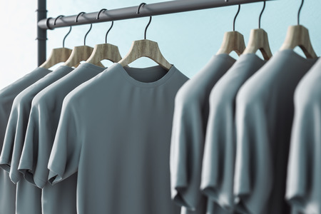 Row of grey t-shirts on hangers. Blue wall background. Style and design concept. 3D Rendering