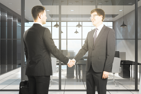 Happy european businessmen shaking hands in modern office interior. Teamwork and deal concept.