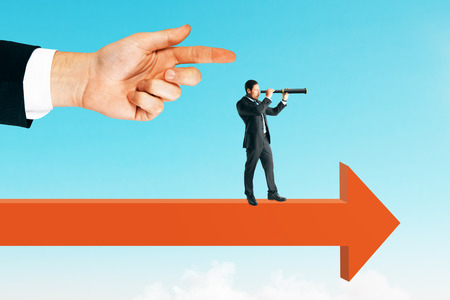 Side view of hand pointing at young businessman looking into the distance while standing on arrow. Sky background. Vision and search concept
