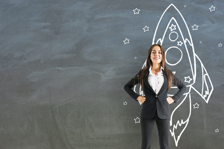 Happy young businesswoman with creative rocket sketch on chalkboard wall background. Startup and business concept