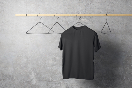Empty one black tshirt on hanger. Concrete wall background. Design, store and style concept. Mock up, 3D Rendering